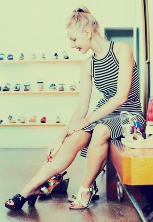 Young  smiling girl trying on chosen shoes in footwear department