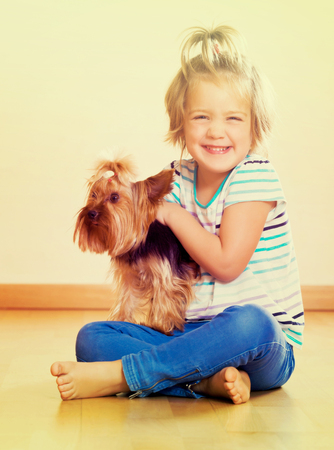 Positive little child holding Yorkshire Terrier and smiling