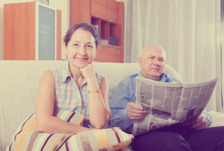 Portrait of smiling joyful family at home on the couch with the newspaper
