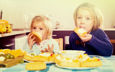 Two happy little girls eating cream desserts at home kitchen