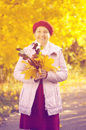 Outdoor portrait of mature woman in autumn with maple posy