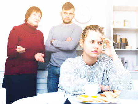 Offended girl dont speaking after discord with mother and brother standing behind