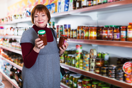 Female consumer holding glass jar of tomato paste in the food shop Stock Photo