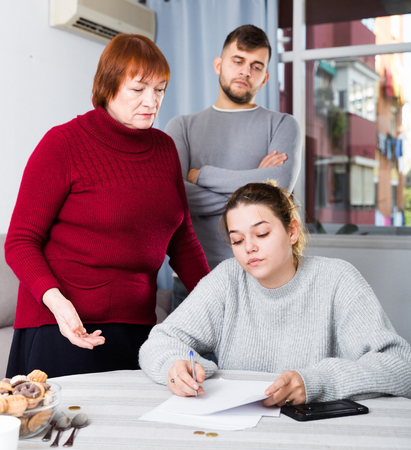 Upset girl sitting with documents while dissatisfied man with older woman standing behind her