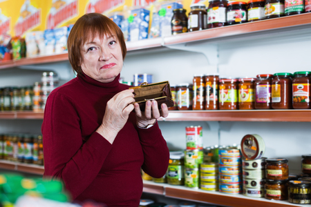 Upset mature female buyer with empty purse in crisis at the food shop Banque d'images