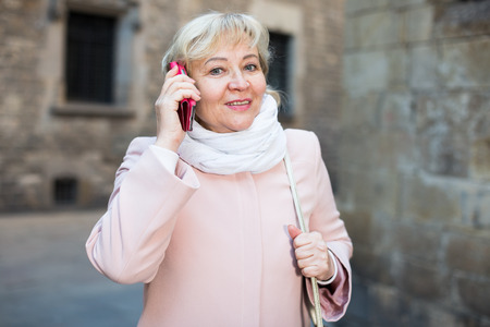 portrait of mature female tourist talking on phone in the center Stock Photo