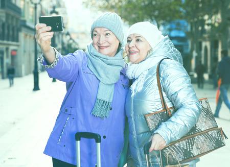Happy elderly women tourists making selfie with phone during walk around city