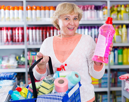 Female holding basket with goods for cleaning house in the household chemical shop Stock Photo