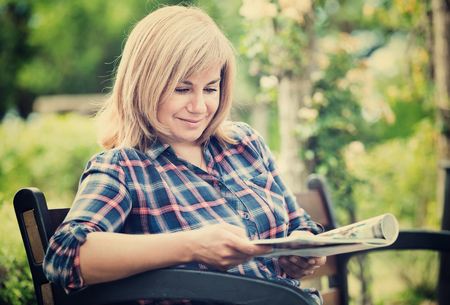 Portrait of cheerful charming mature woman sitting on bench and reading book outdoors in garden