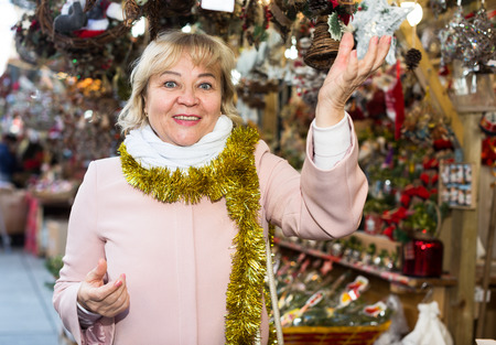 mature tourist female on Christmas Fair looking on decoration Stock Photo