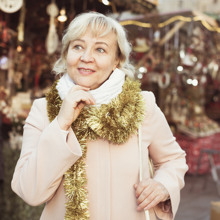 Cheerful adult woman on shiny tinsel among decor on New Years Fair
