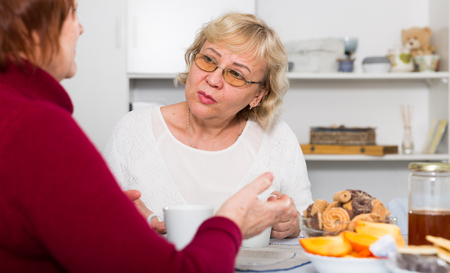 Stressed senior woman having conversation with female over cup of coffee at home 写真素材