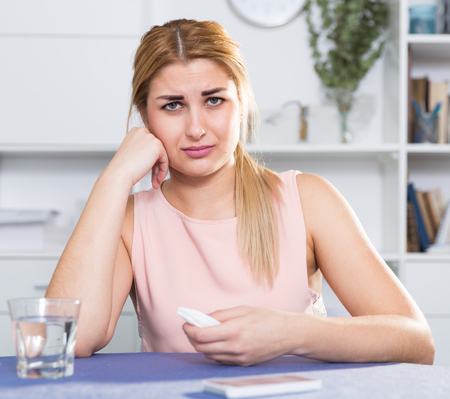 Young female is thoughtful and bored sitting alone at home. Stock Photo