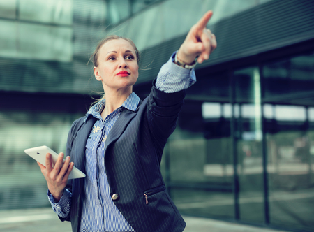 Professional woman in jacket with tablet pointing finger on object  Stock Photo