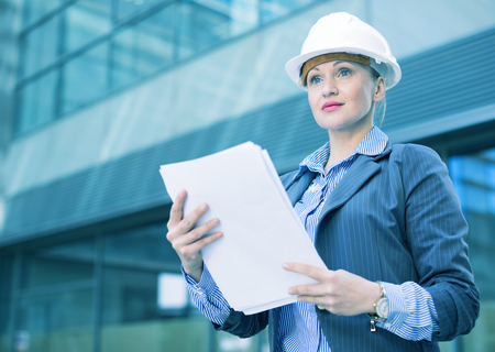 Employee woman in suit standing in helmet with paper documents