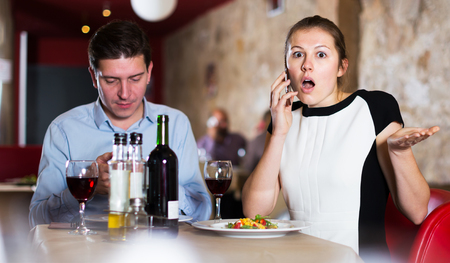 Portrait of woman and man emotionally speaking on phones at restaurant