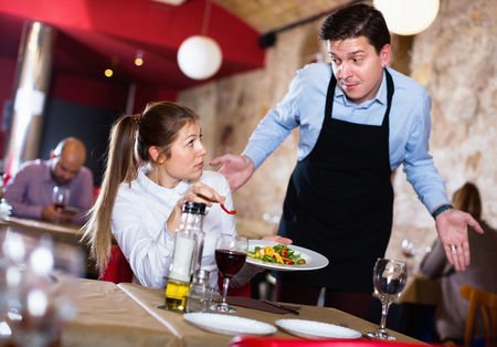 Displeased aggressive young woman conflicting with apologetic waiter because of poor quality of dish in restaurant Stock Photo
