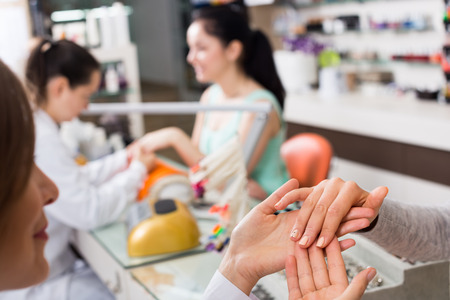 Woman hands in nail salon receiving professional manicure