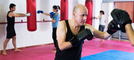 Two male athletes in sportswear practicing boxing sparring at sport class