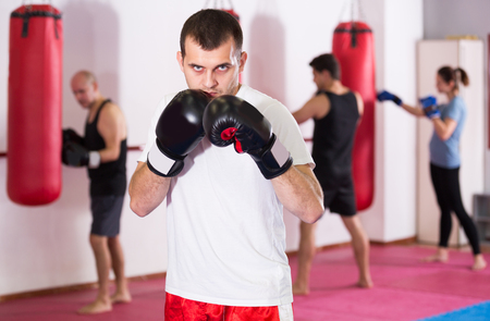 Young male is practicing different kiks in the boxing hall.  Stock Photo