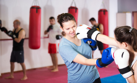 Young sportswomen competing in colored boxing gloves