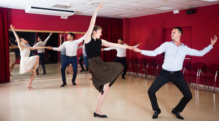 Cheerful people dancing lindy hop in pairs in dance hall Stock Photo
