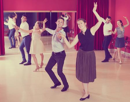 Young dancing couples enjoying latin dances in modern studio Stock Photo