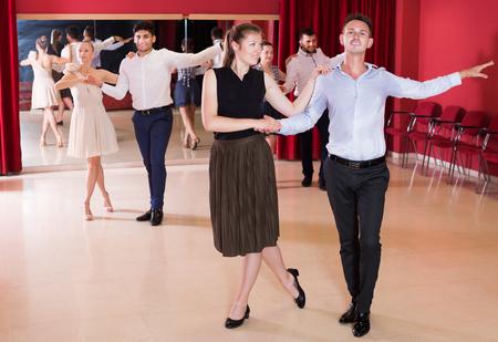 Smiling active dancing couples enjoying latin dances in modern studio Stock Photo