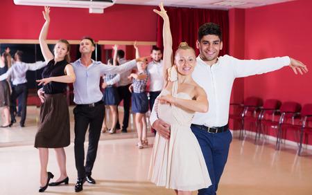 Happy adult couples enjoying latin dances in modern studio