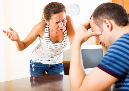 Young couple quarrels sitting at the table at home