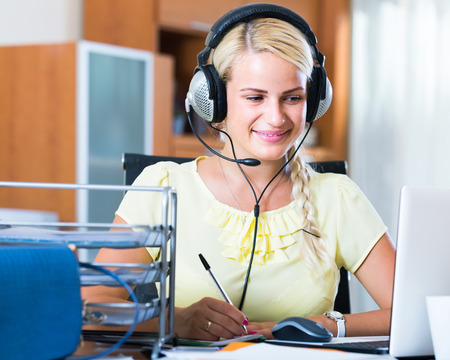 Adult american girl answering the call of technical support and smiling Stock Photo