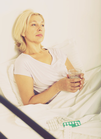 Mature woman laying in bed with pills and glass of water Stock Photo