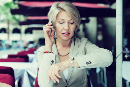 Mature businesswoman is talking on phone with collegue about their meet in time breakfast in cafe.