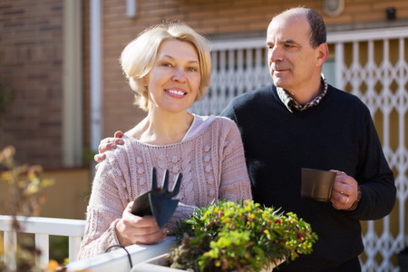 Mature happy female talking with male neighbor at balcon Stock Photo