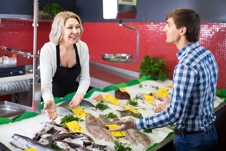 Positive female seller and male customer choosing chilled fish at market