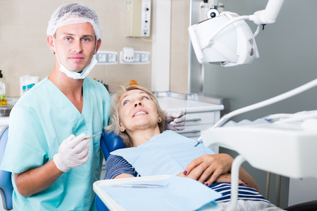 Professional dentist examining and performing treatment to mature woman