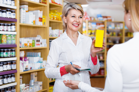 Happy cheerful  mature female seller suggesting care products to young customer in specialized shop Stock Photo