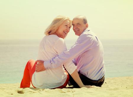 Smiling mature lovers sitting on beach at seashore Stock Photo