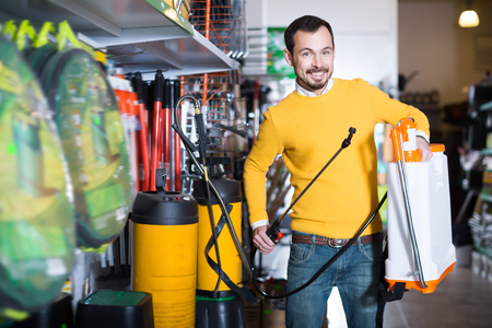 Adult guy deciding on best garden sprayer in garden equipment shop