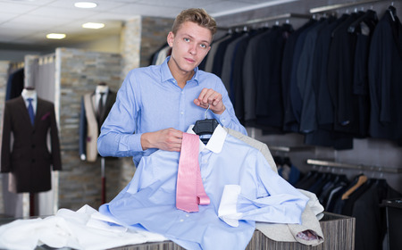 Male purchaser in shirt choosing tie and shirt in the clothes store Stock Photo