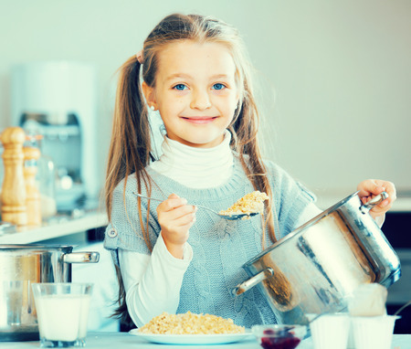 Little girl cooking tasty and healthy porridge in kitchen Stock Photo - 94664575