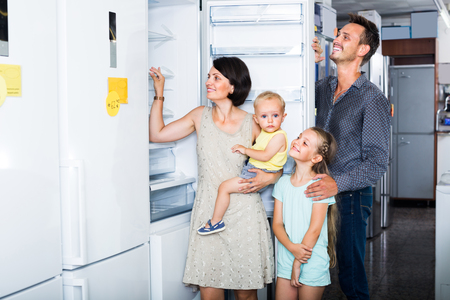smiling family with two children choosing modern fridge in household store Foto de archivo