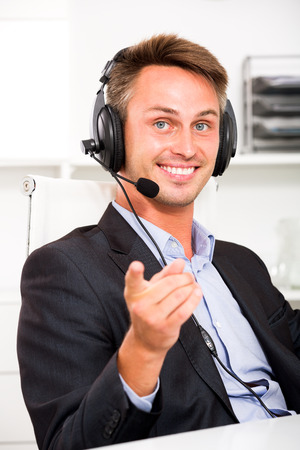 Happy young man talking using hands-free set at customer service office