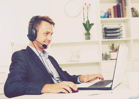 Laughing man talking on headset at company office