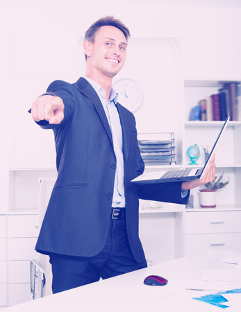 Laughing business man in formalwear standing with laptop in hands in company office Stock Photo