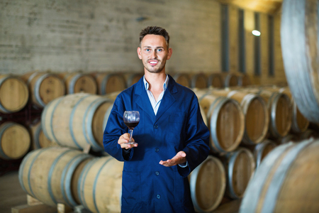 Smiling male young efficient winemaker in uniform having glass of wine in hands in cellar