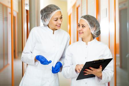 Positive Ärztinnen, die über Schönheitsverfahren in der Schönheitsmedizinmitte sprechen Standard-Bild - 94982503