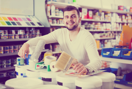 Happy male customer purchasing tools for house improvements in paint supplies store