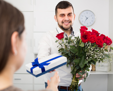 Male worker is presenting flowers to female colleague.