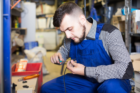 Young worker repairs a plug with a screwdriver in the workshop Stock Photo
